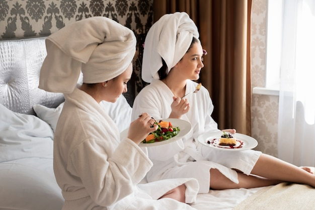 Best friends in robes eating some food Free Photo