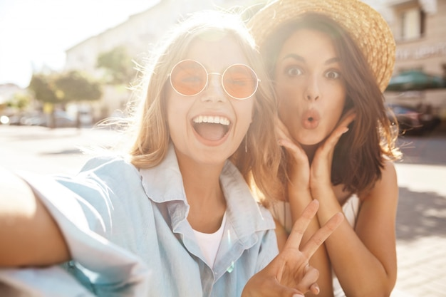 Best friends wearing stylish outfit and taking selfie on the street Free Photo