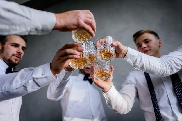 I migliori uomini con gli occhiali pieni di bevande alcoliche vestiti con abiti formali Foto Gratuite