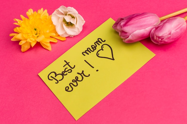 Best mom ever title on yellow paper with buds of flowers Free Photo