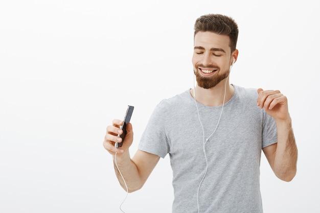 Лучшее музыкальное приложение на свете. радостный харизматичный беззаботный красавец с бородой и больными бровями, закрывающий глаза от восторга и радости, широко улыбаясь, держа смартфон, слушает песни в наушниках, танцует Бесплатные Фотографии
