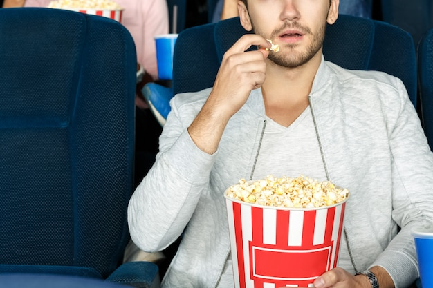 Best snack for cinema. cropped shot of a man eating popcorn in a movie theater Premium Photo