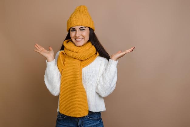 Красивая брюнетка в теплой шапке и варежки на коричневом фоне раскинув руки. Premium Фотографии