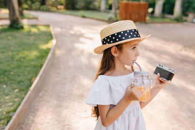 Озадаченная маленькая леди в соломенной канотье держит камеру на улице и смотрит в сторону. открытый портрет милой темноволосой девушки со стаканом апельсинового сока, идущей по переулку. Бесплатные Фотографии