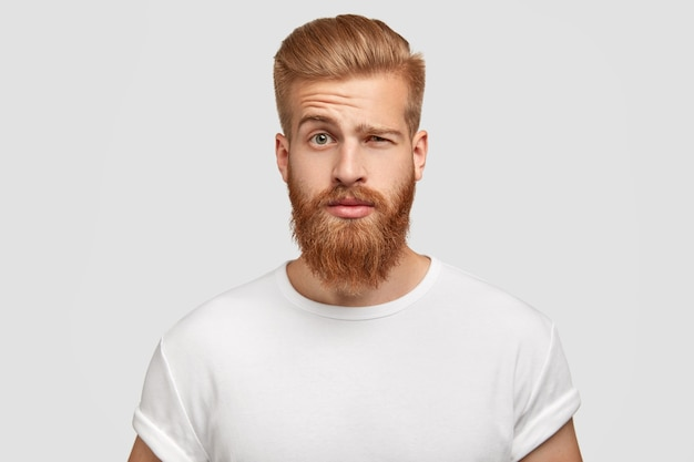 Bewildered man with thick ginger beard, raises eyebrows Free Photo