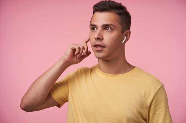 Sconcertato giovane ragazzo piuttosto bruna dagli occhi marroni vestito con una maglietta gialla mantenendo l'indice sollevato sull'auricolare mentre guarda sorpreso avanti, isolato su sfondo rosa Foto Gratuite