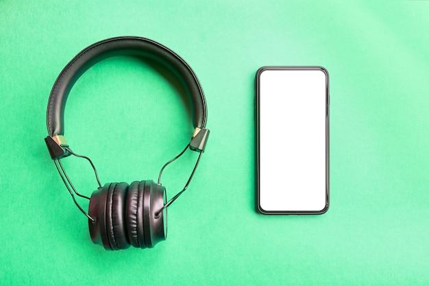 Bezel less mock up smartphone and wireless headphones  on colorful background Premium Photo