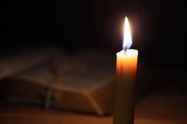 聖書と古いオークの木製テーブルの上のろうそく。 無料写真