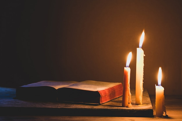 Bible and candle on a old oak wooden table. beautiful gold background. religion concept. Premium Photo