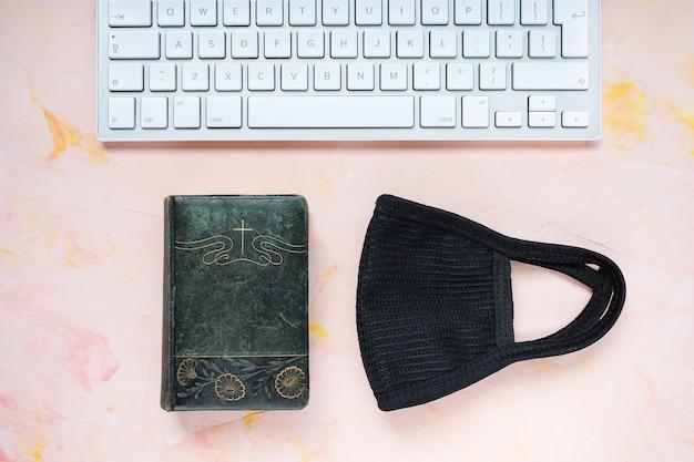 Библия, компьютерная клавиатура и маска на розовом, плоской планировке Premium Фотографии