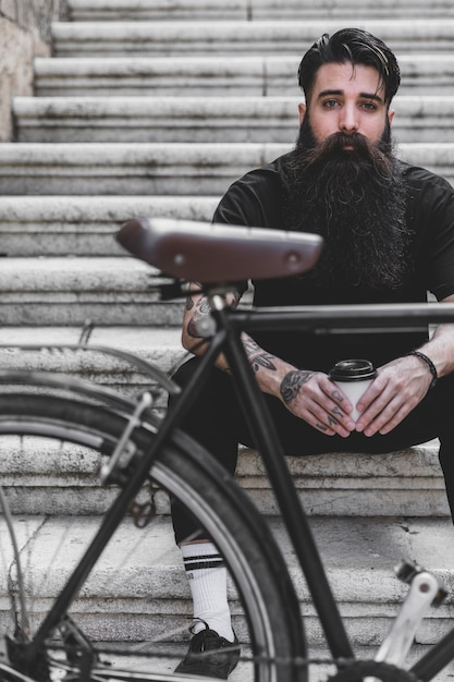 Bicycle in front of a man sitting on staircase holding coffee cup Free Photo