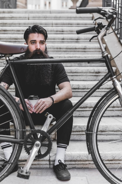 Bicycle in front of a young man sitting on staircase holding takeaway coffee cup Free Photo