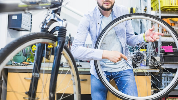 Bicycle mechanic repairing bicycle tire with wrench Free Photo