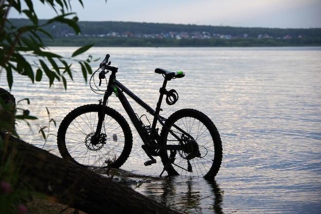 夕日の光の中でビーチで自転車、海の近くの砂丘に自転車を駐車 Premium写真