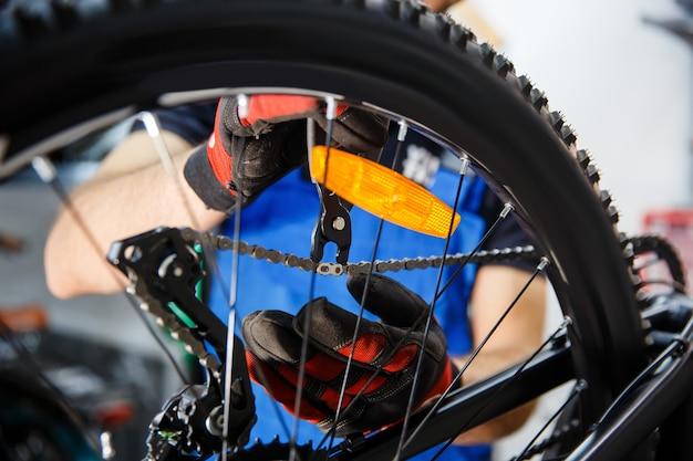 Мастерская по ремонту велосипедов, человек проверяет провисание цепи Premium Фотографии