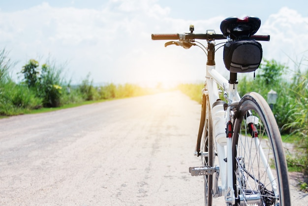 Bicycle on rural road with grass at sunset, countryside of thailand Premium Photo