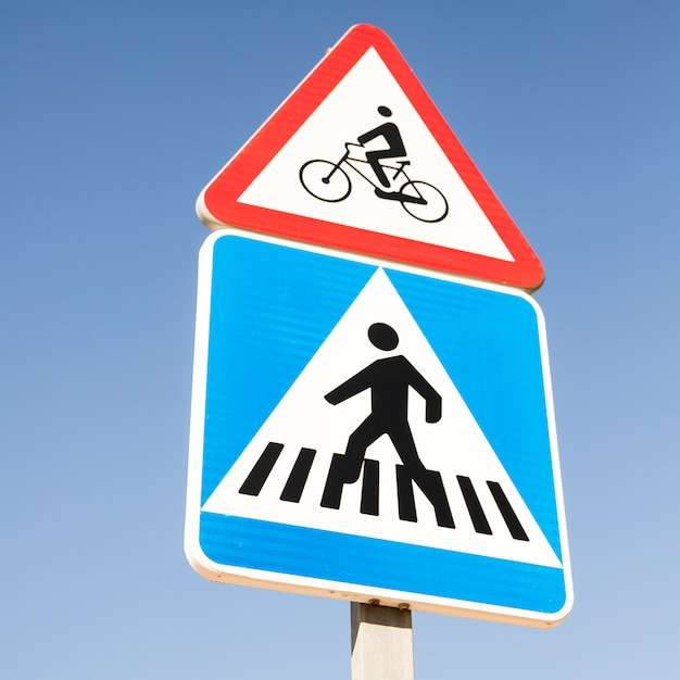 Bicycle warning sign over the modern square pedestrian crossing road sign against blue sky Free Photo