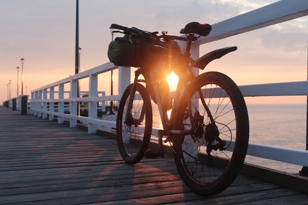 バッグと自転車は日の出、海沿いの桟橋にあります。 Premium写真