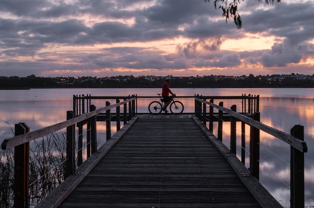 Bicyclist standing on a wooden dock on the water under a cloudy sky during the sunset in the evening Free Photo