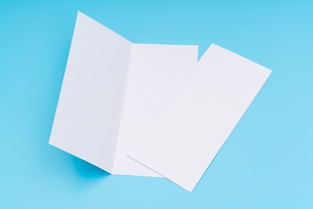 Bifold white template paper on blue background . Free Photo
