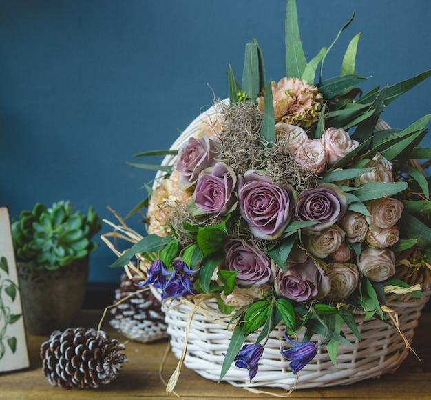 Big basket of mixed flowers standing on a table with christmas cones Free Photo