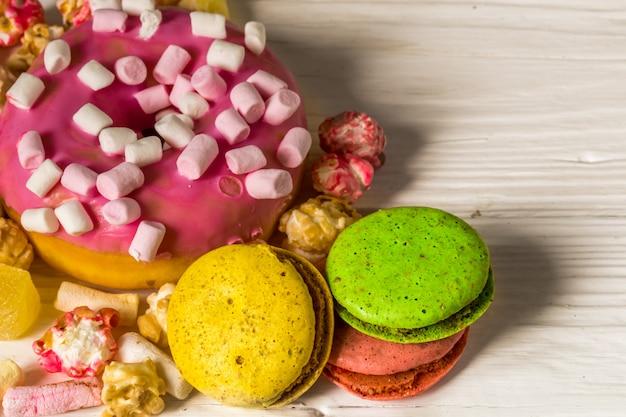 木製のテーブルにお菓子と大きな美しいピンクボックス 無料写真