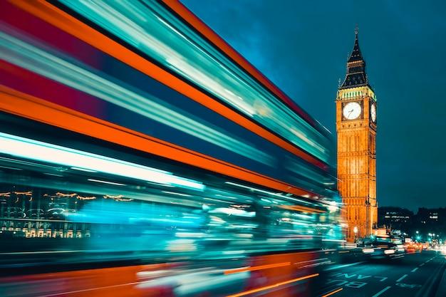 Биг бен, один из самых ярких символов лондона и англии, изображенный ночью вместе с огнями проезжающих мимо автомобилей. Premium Фотографии