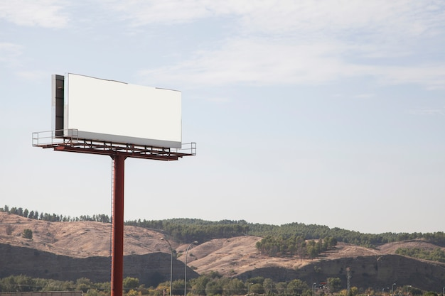 Big billboard advertising sign with mountains and sky in the background Free Photo