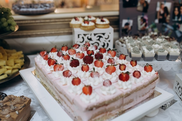 Big biscuit cake with cream and strawberries cutted on portions Free Photo