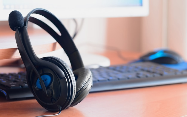 Big black headphones lie on the wooden desktop of the sound designer Premium Photo