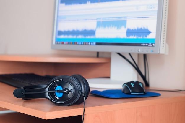 Big black headphones lying on wooden desktop with computer screen Premium Photo