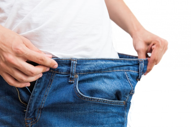 Big blue jeans for thin man. man holding jeans in hands on white background. Premium Photo