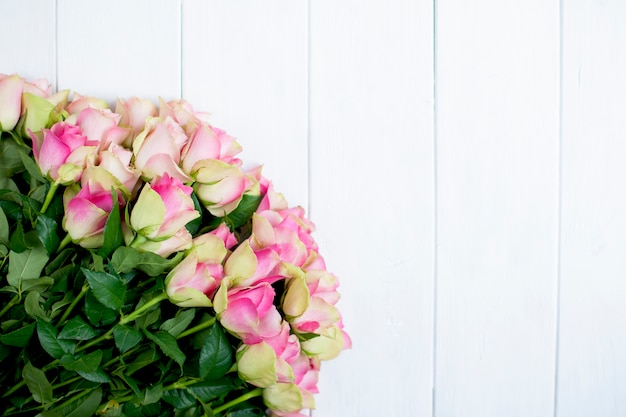 Big bouquet of roses with pink petals and green on white wooden background Premium Photo