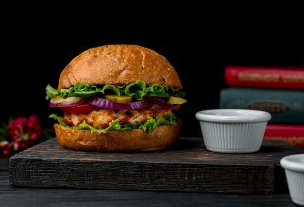 Big burger stuffed with chicken meat and salad on a wooden board. Free Photo