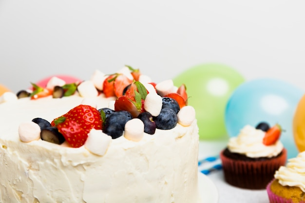 Big cake with different berries near cupcakes on table Free Photo