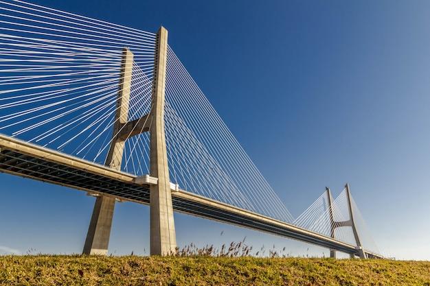 Grande ponte del cemento su un campo sotto il chiaro cielo blu Foto Gratuite