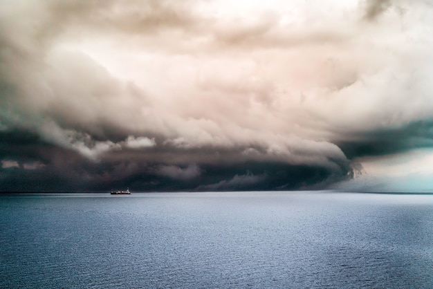 Big dark clouds covering the pure ocean with a ship sailing in it Free Photo