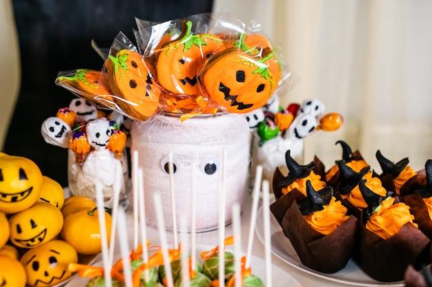 Большая украшенная баночка с тыквенным зефиром на моноблоке для празднования хэллоуина. Premium Фотографии