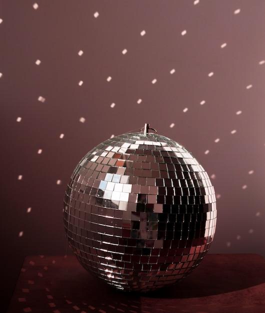 Big disco ball on brown floor with lights Free Photo