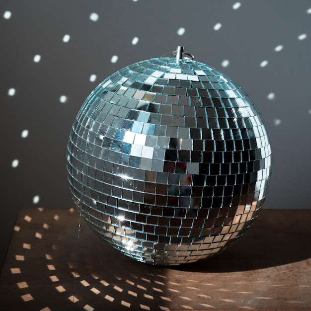 Big disco ball on brown floor with party lights Free Photo