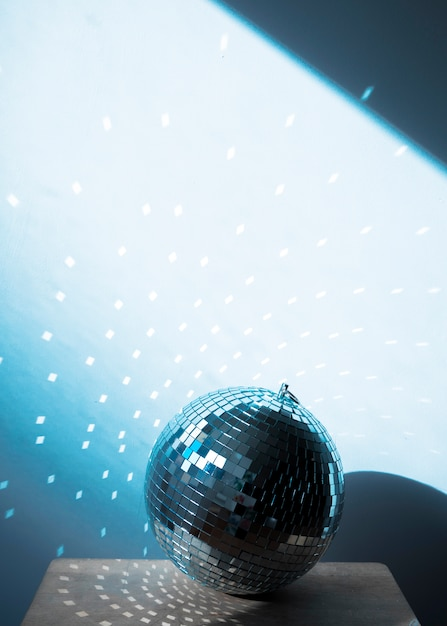 Big disco ball on chair with party lights Free Photo