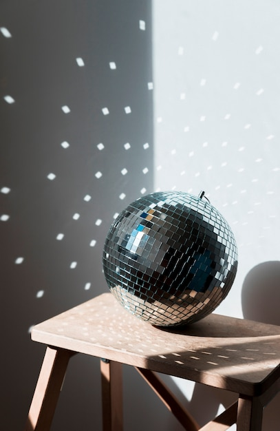 Big disco ball on wooden chair Free Photo