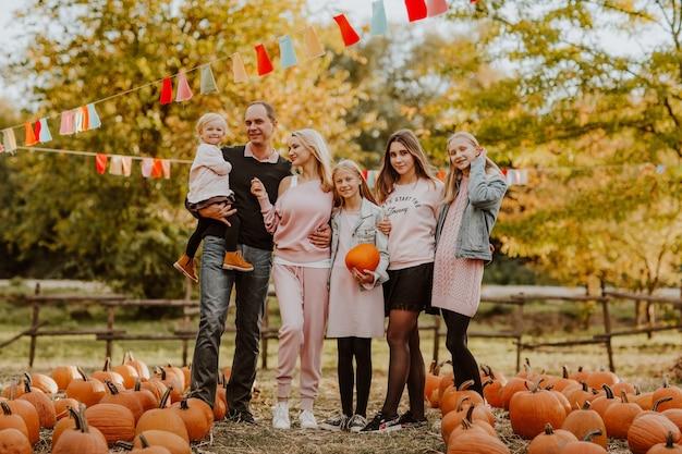 Большая семья проводит время на тыквенной ферме. время падения Premium Фотографии