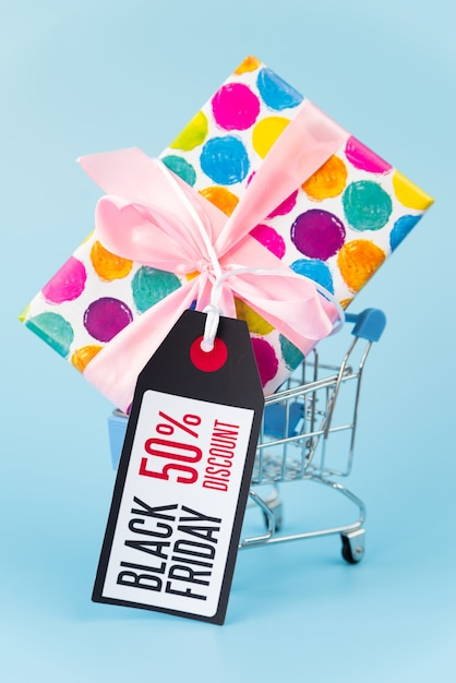 Big gift in shopping cart with tag Free Photo