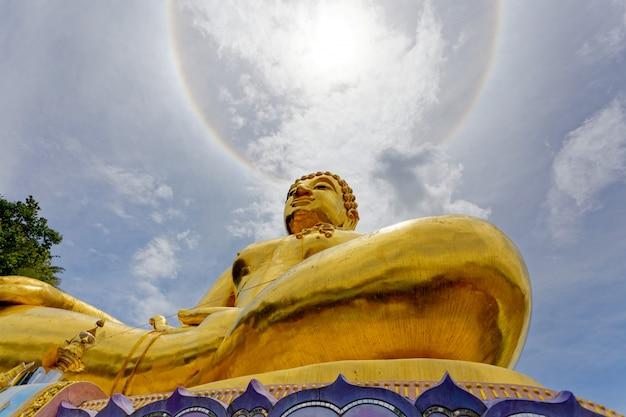 Big gold statue buddha under the corona ring sun light. Premium Photo