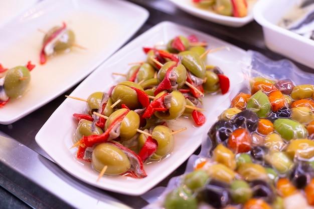 さまざまな詰め物のシーフード、肉を使ったスティックに大きな緑色の新鮮な熟したオリーブ Premium写真