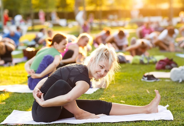 Big group of adults attending a yoga class outside in park Premium Photo