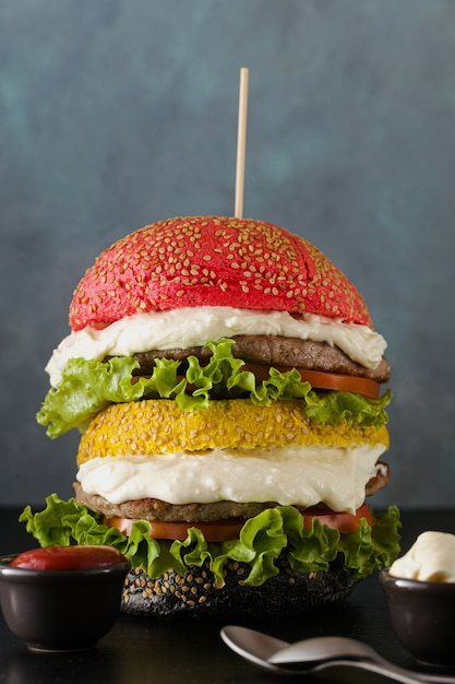 Big hamburgers with different colors bread buns in red , yellow and black with parmesan cream and tomatoes, salad on the table. Premium Photo