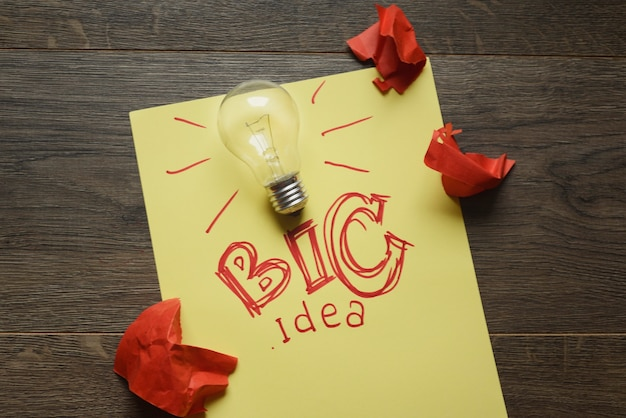 Big idea with lightbulb and red crumpled papers Premium Photo