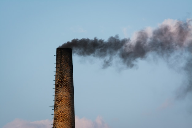 Big industrial pipe made of brick with black smoke going outside Premium Photo